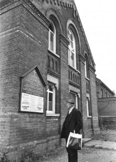 The Congregational Church became Christ Church in 1970. This photograph was taken a short while before the church was demolished to make way for shop and office development. It shows Mr Ivan Pickman reading the notices which advised visitors to use Wesley Hall, in Southend Road, or St. Andrews, in London Road.