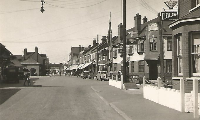 This photograph may have been taken in the 1930's or 1940's as the cars parked on the street are from that era. The Swan is on the right, you can just see the turning into Swan Lane. There is a petrol station on the nearside of the road, on the right.
