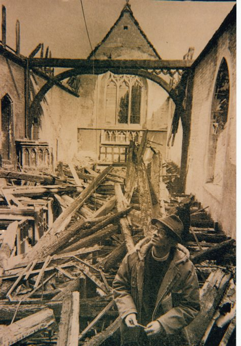 Rev. Pettitt in the burnt out shell of the church | Downham Church Collection