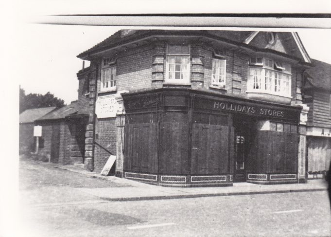 This picture shows Hollidays store with the shutters down.Possibly taken during war time