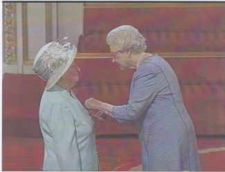 Audrey being presented with the MBE by the Queen