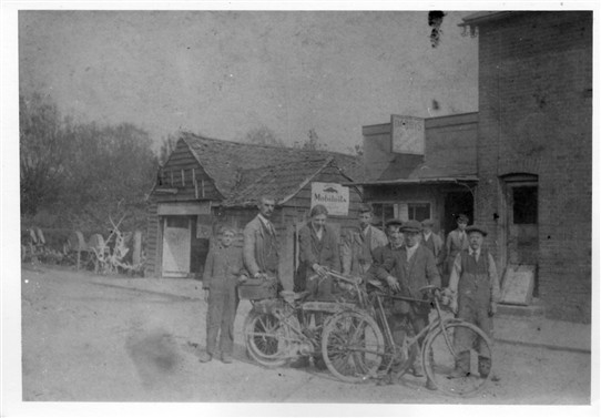 Outside Darby's factory c.1918.  The small boy on the left is Mr Bill Lepper.  The man holding the motorcycle handle is Mr Stan Nicholls, at one time Essex and England cricketer.