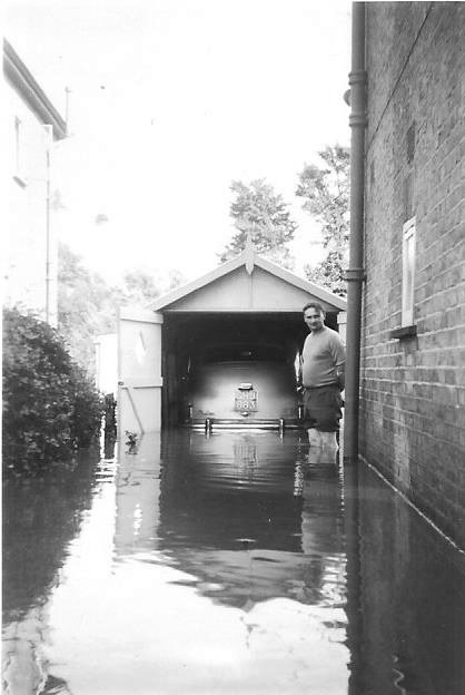 John's father at the side of the house, with the Standard Vanguard in the garage. Was that a high water mark of the flood just below the window?  | John Potton