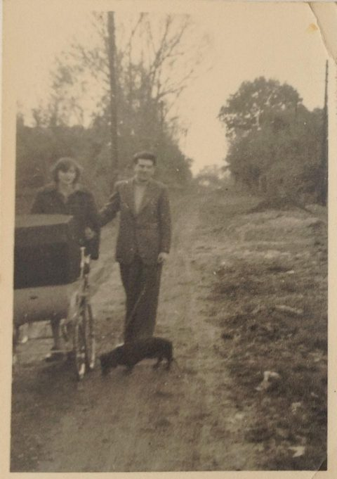Walking along Belmont Avenue in 1958. Daphne and Peter White with their dachshund, Mandy. Nicholas is in the pram.